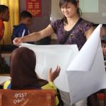 Jennifer passing out paper to make kites